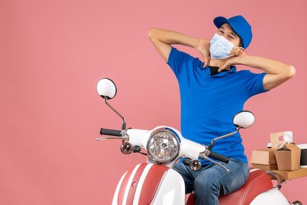 Vooraanzicht van een positieve koeriersman met een medisch masker met een hoed die op een scooter zit en bestellingen aflevert op een pastelkleurige perzikachtergrond