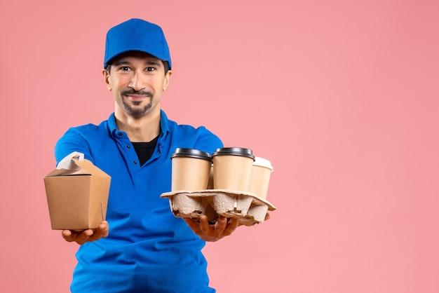 Vooraanzicht van een positieve mannelijke bezorger die een hoed draagt die bestellingen geeft