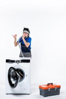 Vooraanzicht van een reparateur in uniform die achter een witte wasmachine staat die pijp op een witte geïsoleerde muur blaast