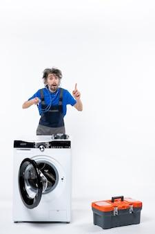 Vooraanzicht van een reparateur met een stethoscoop die achter de wasmachine op een witte muur staat