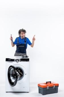 Vooraanzicht van een reparateur met een stethoscoop die achter de wasmachine staat en naar rechts wijst op de witte muur