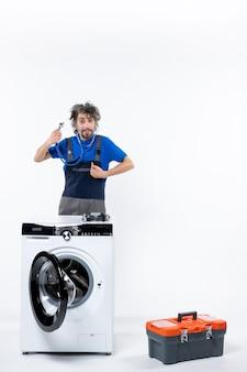 Vooraanzicht van een reparateur met een stethoscoop die naar zichzelf wijst en achter de wasmachine op een witte muur staat