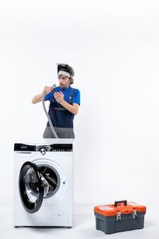 Vooraanzicht van een reparateur met grote ogen in uniform staande achter de wasmachine die de pijp op de witte muur controleert