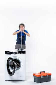 Vooraanzicht van een reparateur met grote ogen in uniform staande achter de wasmachine die pijp op de witte muur blaast