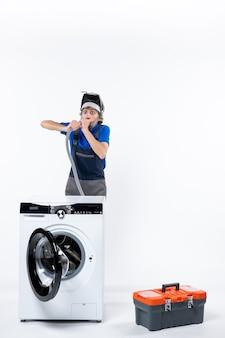 Vooraanzicht van een reparateur met grote ogen in uniform staande achter de wasmachine die plastic pijp op de witte muur uitblaast