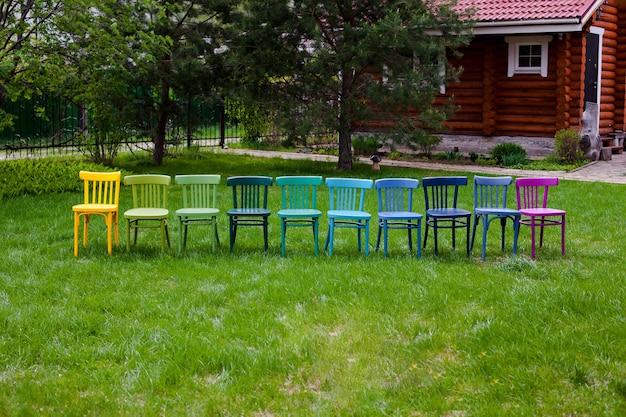 Vooraanzicht van een rij houten veelkleurige stoelen op het groene gras van de tuin met een blokhut ...
