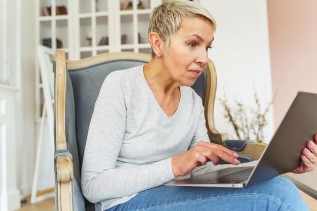 Vooraanzicht van een senior kortharige blanke vrouwelijke freelancer die met grote ogen naar het laptopscherm staart