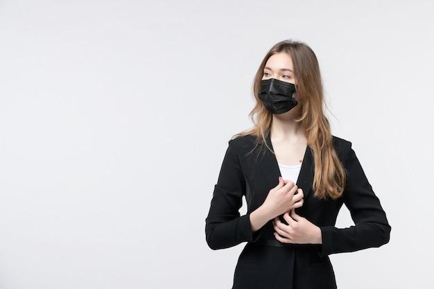 Vooraanzicht van een serieuze jonge dame in pak die een chirurgisch masker draagt en naar iets op wit kijkt