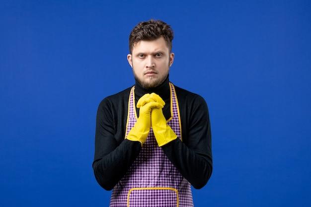 Vooraanzicht van een serieuze jonge man die de handen ineen slaat op de blauwe muur