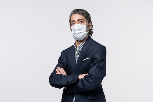 Vooraanzicht van een serieuze jonge man in een pak met een masker op een witte ondergrond