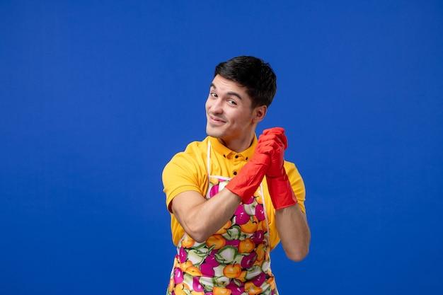Vooraanzicht van een tevreden huishoudster die zijn handen samenvoegt en op een blauwe muur staat