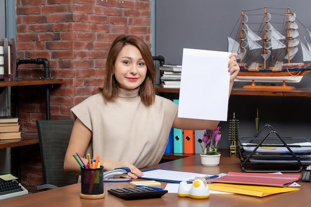 Vooraanzicht van een tevreden vrouw die documenten omhoog houdt die aan de muur zitten