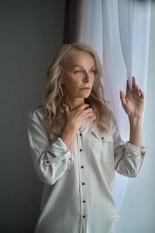 Vooraanzicht van een trieste peinzende moedeloze aantrekkelijke elegante volwassen vrouw die een raamgordijn aanraakt