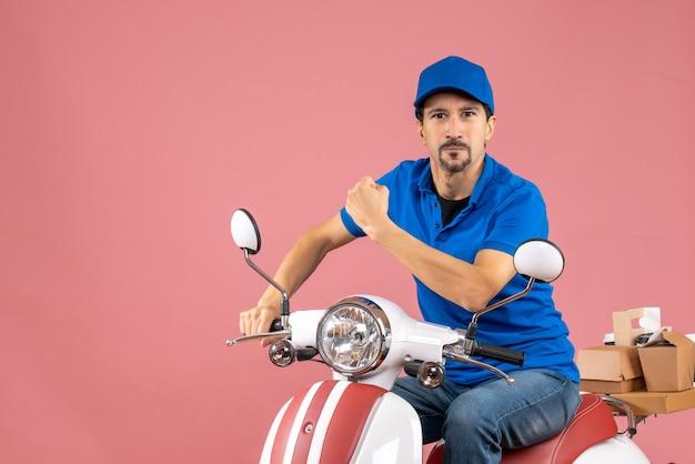 Vooraanzicht van een trotse koeriersman met een hoed die op een scooter zit op een pastelkleurige perzikachtergrond