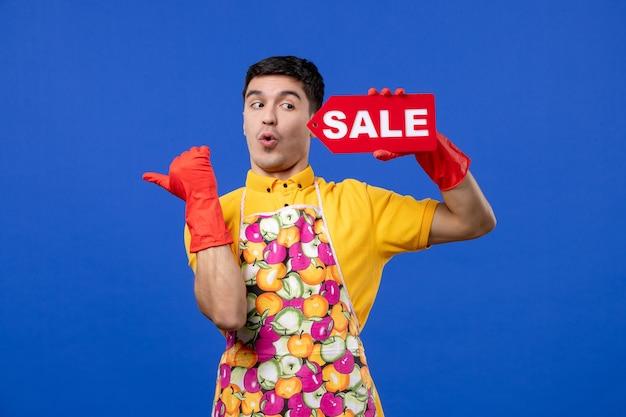 Vooraanzicht van een verbaasde huishoudster met rode afvoerhandschoenen met een verkoopbord dat naar links op de blauwe muur wijst