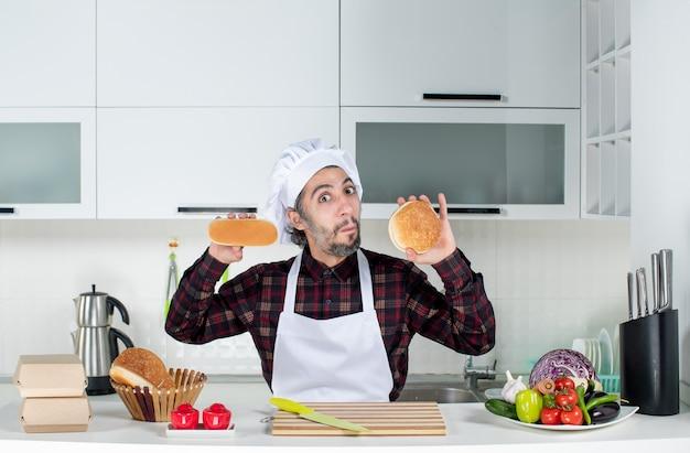 Vooraanzicht van een verbaasde mannelijke chef-kok die brood in beide handen in de keuken houdt