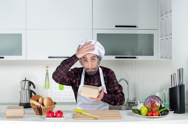 Vooraanzicht van een verbaasde mannelijke chef-kok die een hamburgerdoos in de keuken vasthoudt