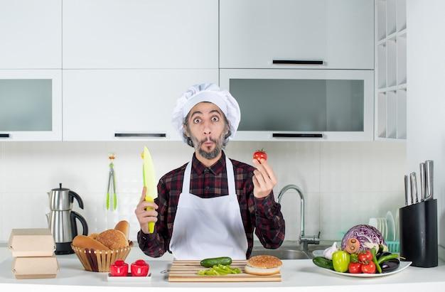 Vooraanzicht van een verbaasde mannelijke chef-kok met tomaat en mes in de keuken