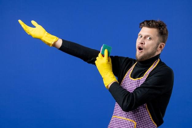 Vooraanzicht van een verbaasde mannelijke huishoudster die een spons vasthoudt die op een blauwe muur staat