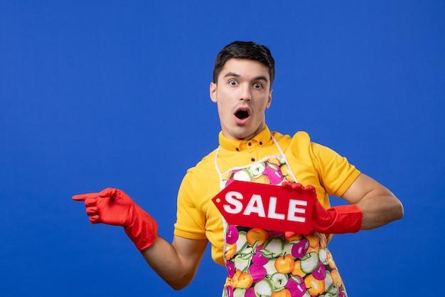 Vooraanzicht van een verbaasde mannelijke huishoudster in een geel t-shirt met een verkoopbord dat naar links op de blauwe muur wijst