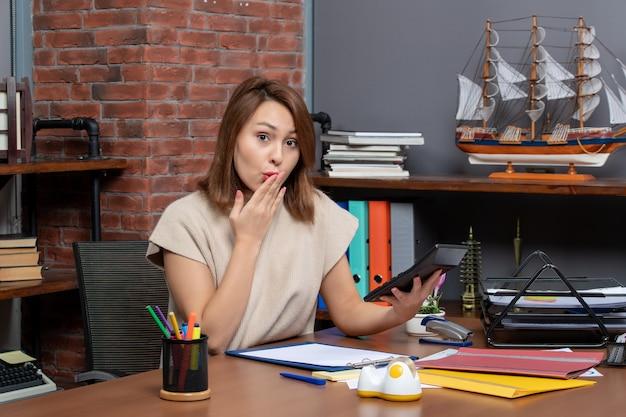 Vooraanzicht van een verbaasde vrouw met een rekenmachine die op kantoor zit