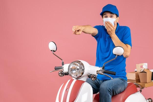 Vooraanzicht van een verraste bezorger met een medisch masker met een hoed die op een scooter zit en naar voren wijst op een pastelkleurige perzikachtergrond