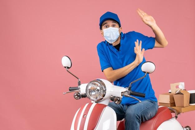 Vooraanzicht van een verraste bezorger met een medisch masker met een hoed op een scooter op een pastelkleurige perzikachtergrond