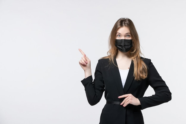 Vooraanzicht van een verraste jonge dame in pak die een chirurgisch masker draagt en op wit wijst