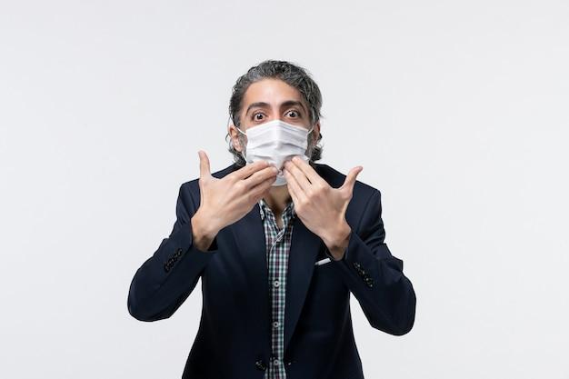 Vooraanzicht van een verraste jonge kerel in pak met een masker en zijn mond wijzend op een wit oppervlak