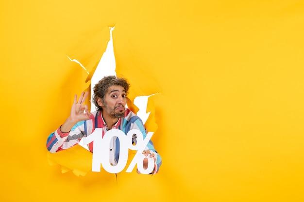 Vooraanzicht van een verraste jonge man die tien procent toont en een brilgebaar maakt in een gescheurd gat in geel papier