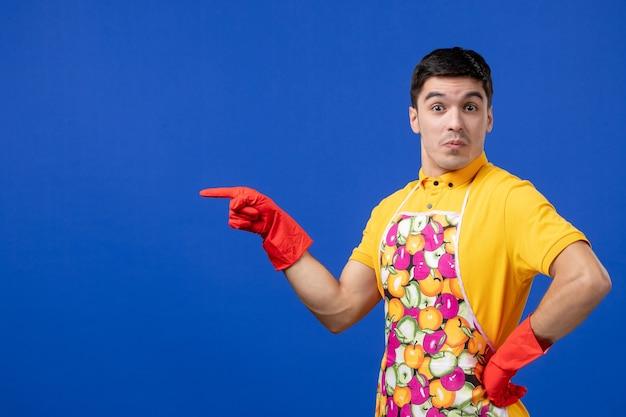 Vooraanzicht van een verraste mannelijke huishoudster in een schort die de hand op een taille legt die op een blauwe muur staat