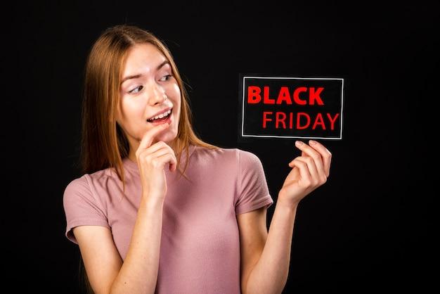 Vooraanzicht van een verraste vrouw die de zwarte vrijdagkaart bekijkt