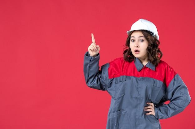 Vooraanzicht van een verraste vrouwelijke bouwer in uniform met harde hoed en naar boven gericht op geïsoleerde rode achtergrond