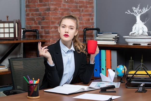 Vooraanzicht van een verwarde jonge vrouw die aan een tafel zit en een rode kop vasthoudt op kantoor