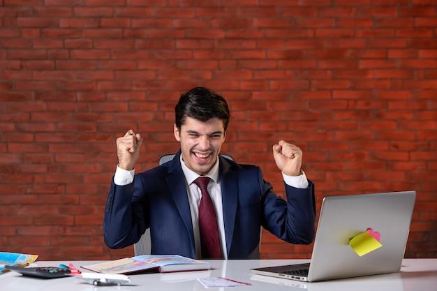 Vooraanzicht van een vreugdevolle reisagent die achter zijn werkplek in pak zit en laptop gebruikt bedrijfsbezetting dienst toerisme overzee globaal agentschap assistent project