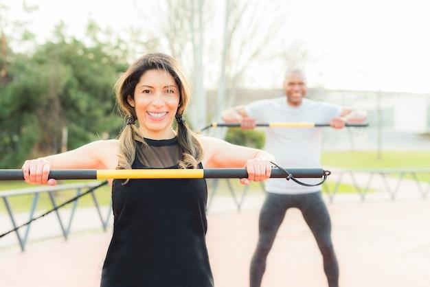 Vooraanzicht van een vrolijk fitnesspaar dat traint met een elastische gymstok in het park. multi-etnische mensen die buiten sporten.