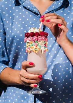 Vooraanzicht van een vrouw die een milkshake houdt