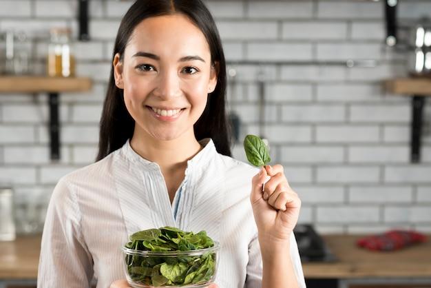 Vooraanzicht van een vrouw die gezonde basilicumbladeren toont