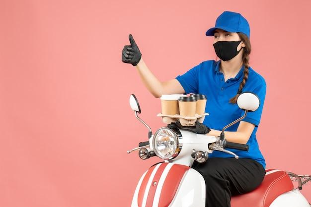 Vooraanzicht van een vrouwelijke bezorger met een medisch masker en handschoenen die op een scooter zit en bestellingen vasthoudt die omhoog wijzen op een pastelkleurige perzikachtergrond