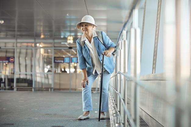 Vooraanzicht van een vrouwelijke toerist met een wandelstok die plotselinge kniepijn ervaart op de luchthaven