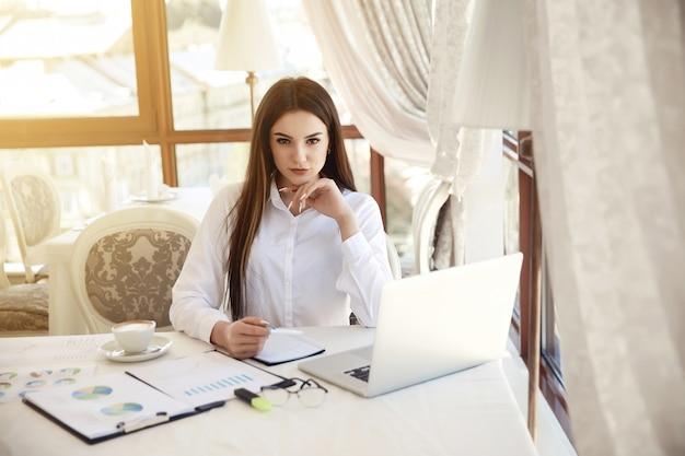 Vooraanzicht van een werkplek met een jonge mooie brunette vrouw die recht kijkt, omringd met veel diagrammen