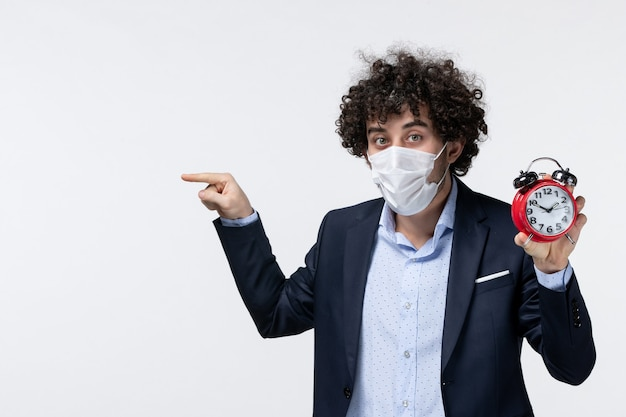 Vooraanzicht van een zakenman in pak en zijn masker dragend met een klok die iets aan de rechterkant wijst