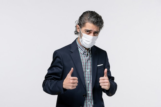 Vooraanzicht van een zelfverzekerde jonge kerel in pak die een masker draagt en een goed gebaar maakt op een witte ondergrond