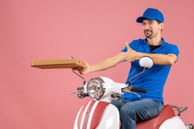Vooraanzicht van een zelfverzekerde koeriersman met een hoed die op een scooter zit en de bestelling vasthoudt en een goed gebaar maakt op een pastelkleurige perzikachtergrond