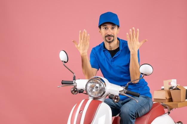 Vooraanzicht van een zelfverzekerde koeriersman met een hoed die op een scooter zit en tien laat zien op een pastelkleurige perzikachtergrond