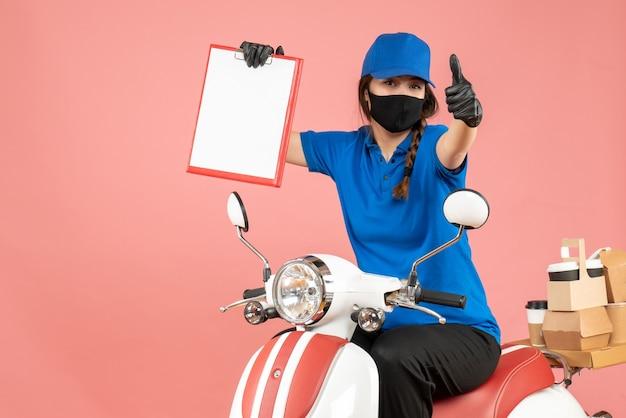 Vooraanzicht van een zelfverzekerde koeriersvrouw met een medisch masker en handschoenen die op een scooter zit en lege vellen papier vasthoudt die bestellingen afleveren en een goed gebaar maakt op een pastelkleurige perzikachtergrond