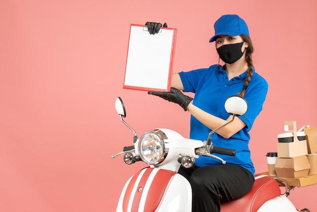 Vooraanzicht van een zelfverzekerde koeriersvrouw met een medisch masker en handschoenen die op een scooter zit en lege vellen papier vasthoudt die bestellingen afleveren op een pastelkleurige perzikachtergrond