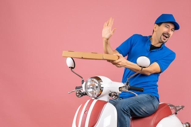 Vooraanzicht van een zich afvragende koeriersman met een hoed die op een scooter zit en de bestelling vasthoudt op een pastelkleurige perzikachtergrond