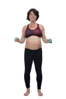Vooraanzicht van een zwangere vrouw die oefenweerstandsbanden doet op een witte achtergrond