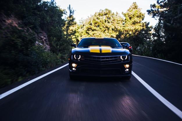 Vooraanzicht van een zwarte sportwagen met twee gele strepen erop.